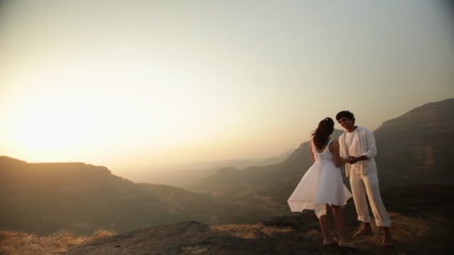 young couple romancing on a cliff of a mountain  - romantic sky stock videos & royalty-free footage