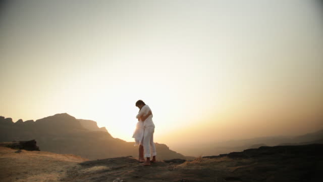 stockvideo's en b-roll-footage met young couple romancing on a cliff of a mountain  - vignettering