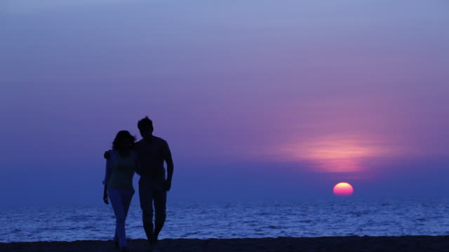 Young couple romancing on the beach at sunset