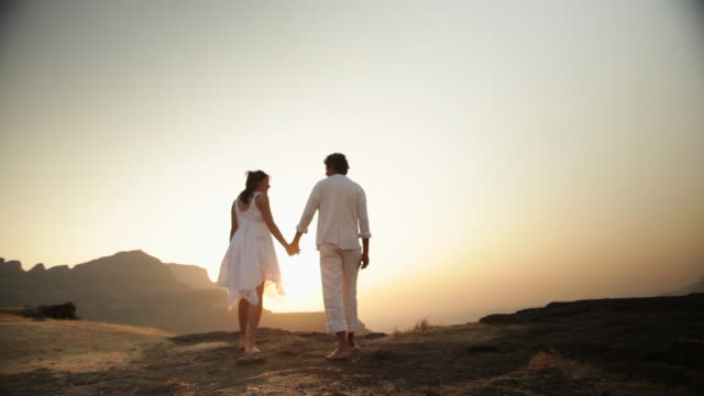 young couple romancing on the cliff of mountain - romantic sky stock videos & royalty-free footage