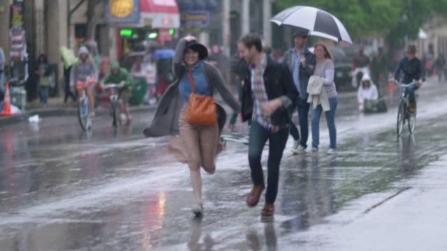 vídeos de stock e filmes b-roll de young couple run across the street in the rain - chuva
