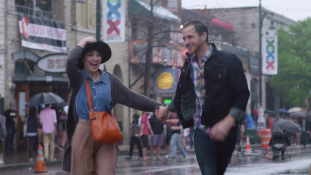 young couple run across the street in the rain - rain stock videos & royalty-free footage