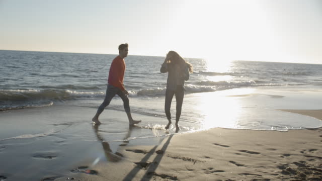 Young couple running along beach towards camera