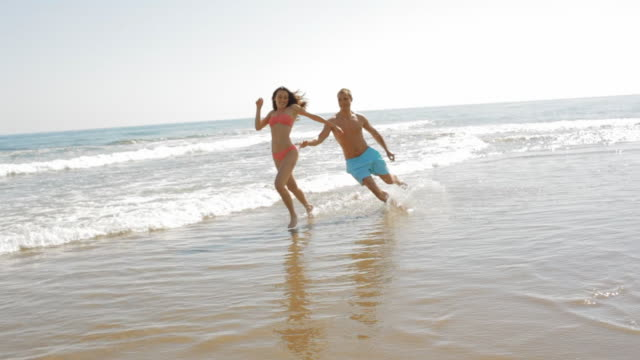 young couple running and chasing on the beach - 水泳パンツ点の映像素材/bロール