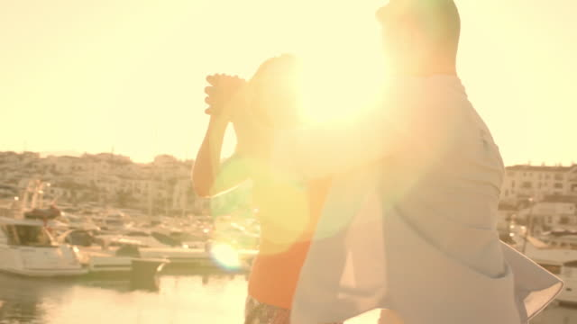 young couple running  and dancing by marina in sunset. - slow dancing stock videos and b-roll footage