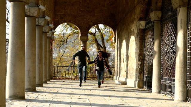 vídeos de stock e filmes b-roll de casal jovem correr e saltar com colunas-slowmotion antiga - corredor caraterística de construção