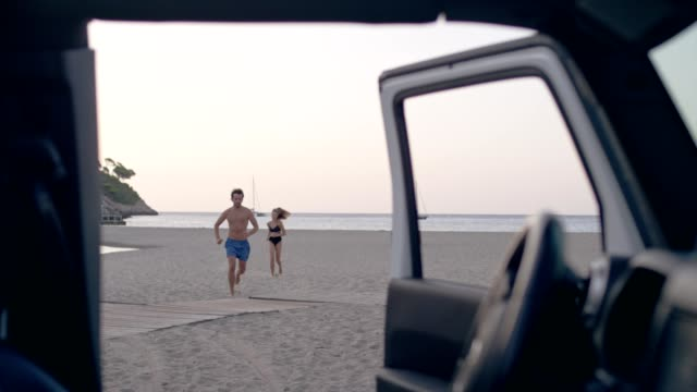 young couple running away from car to the beach - 4x4 stock videos & royalty-free footage