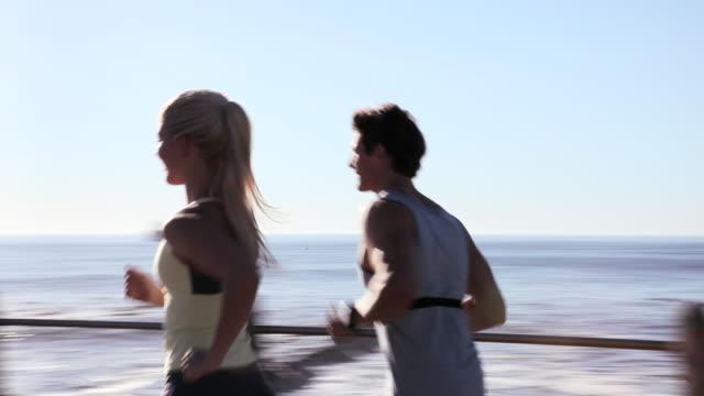 vídeos de stock, filmes e b-roll de young couple running by sea - calções de corrida