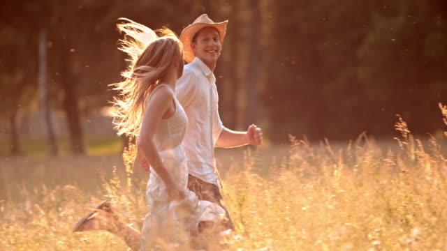 vídeos de stock, filmes e b-roll de slo mo t casal jovem correr na grama alta - casal jovem