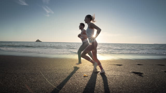 young couple running on beach at sunset, bandon, oregon - arrivo video stock e b–roll