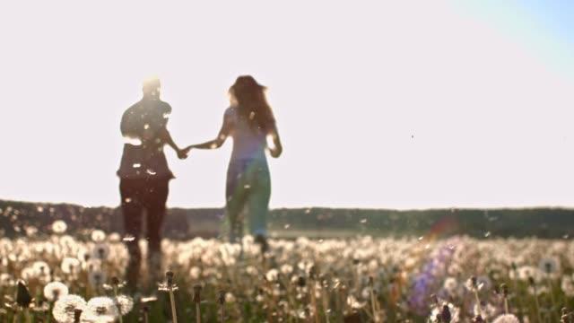 SLO MO Young couple running through dandelion seeds