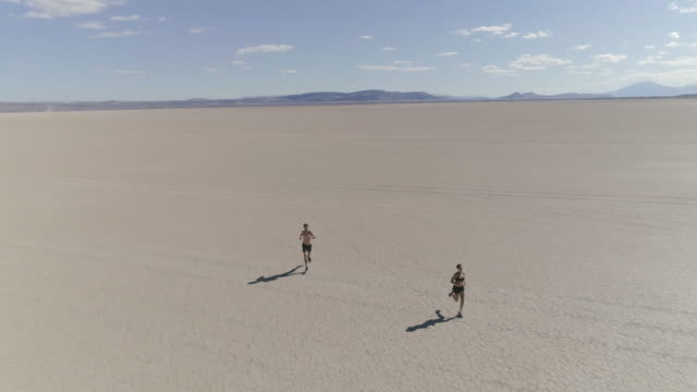 Young couple running through the dessert