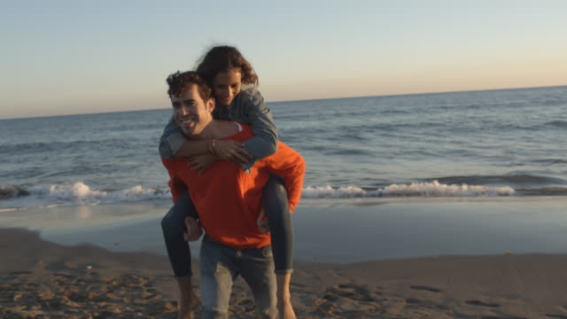 Young couple running to camera on beach, man carrying woman