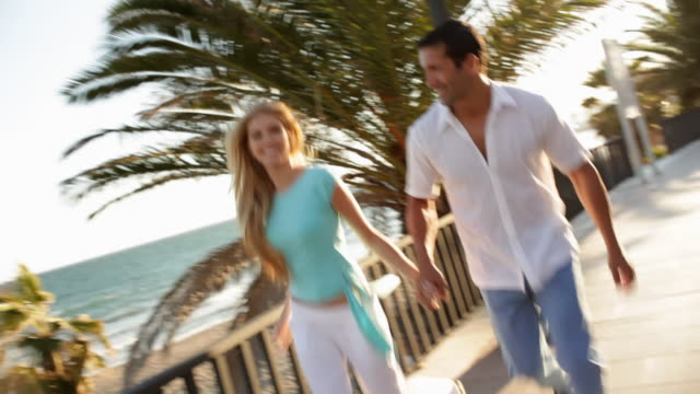 young couple running towards camera - 膝から上の構図点の映像素材/bロール