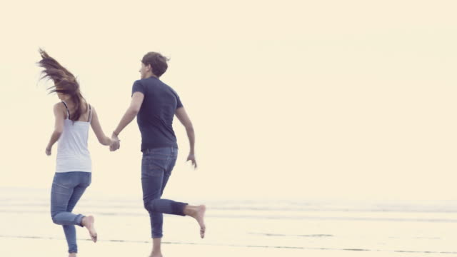 A young couple running whilst holding hands on the beach at Porthmadog