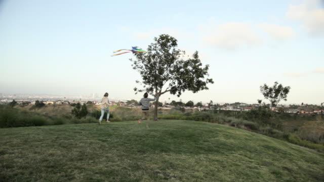 vidéos et rushes de young couple running with kite in field - jeune d'esprit