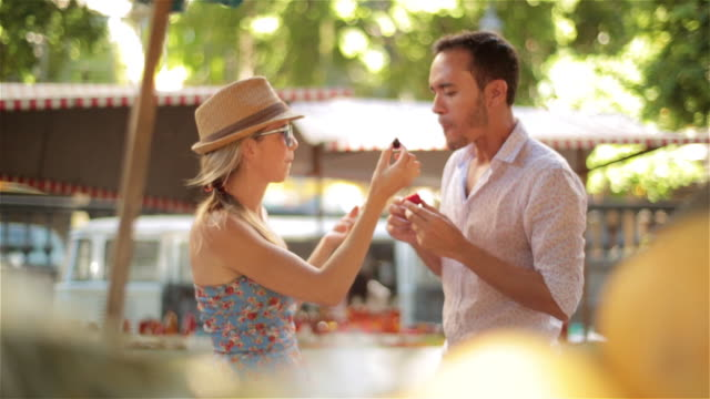 Young couple sample fruit in sunny Brazilian market