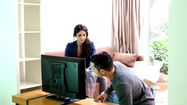 young couple set new lcd television in living room - liquid crystal display television stock videos and b-roll footage