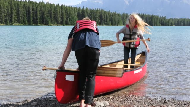 young couple set out in canoe, from beach at mtn lake - kanu stock-videos und b-roll-filmmaterial