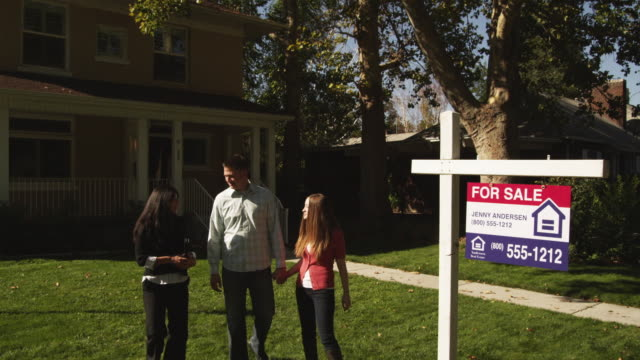 ws td young couple shaking hands with real estate agent and hugging in front of suburban house with 'for sale' sign on lawn / provo, utah, usa - estate agent sign stock videos & royalty-free footage