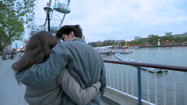 young couple share a kiss walking towards the london eye on the south bank. - millennium wheel stock videos & royalty-free footage