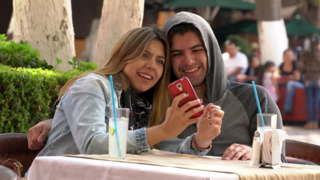 Young couple shares big laugh in outdoor cafe