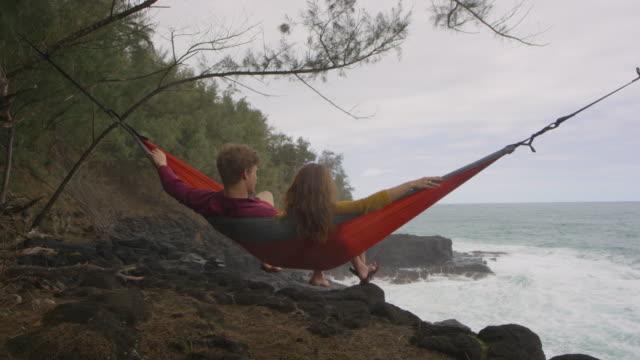 Jong koppel delen een hangmat naast de golven