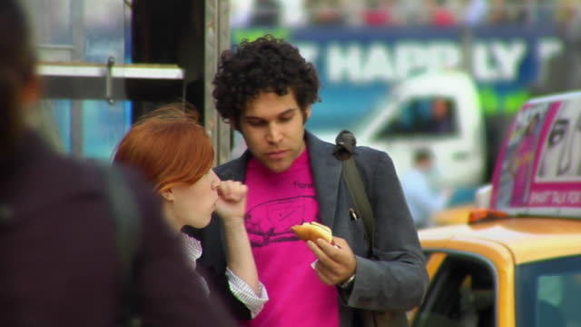 ms young couple sharing a hot dog on the street/ new york city - hot dog stock videos & royalty-free footage