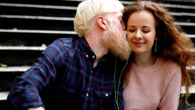 young couple sharing earphone and listening music from mobile phone - kissing stock videos & royalty-free footage