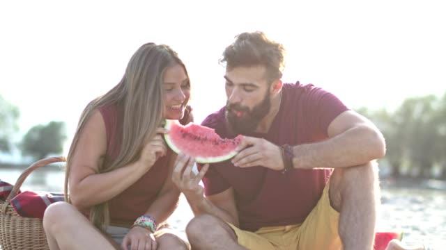 vídeos de stock, filmes e b-roll de jovem casal partilha melancia na praia - fruta