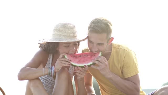 Young couple sharing watermelon at the beach