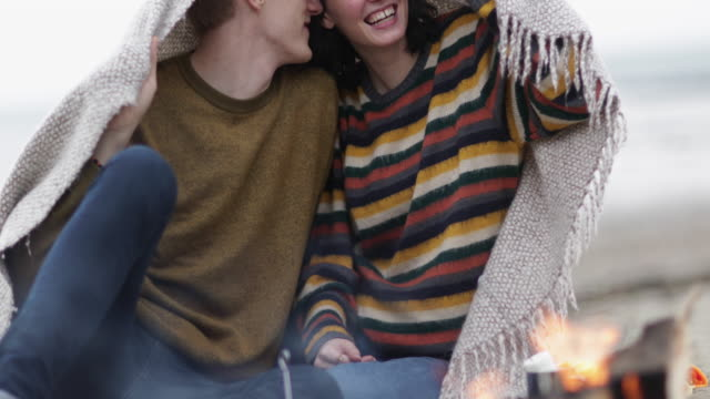 vidéos et rushes de young couple sheltering from rain under a blanket - protection