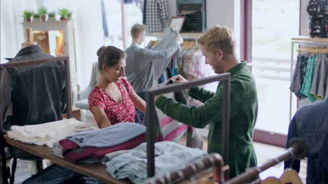 young couple shop in local clothing store - boutique stock videos & royalty-free footage