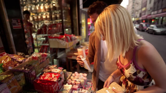 SLO MO, SELECTIVE FOCUS, Young couple shopping for nuts and dried fruit at storefront in Chinatown, New York City, New York, USA