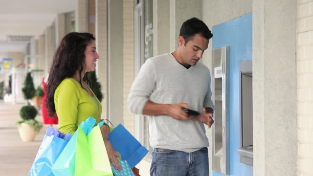 stockvideo's en b-roll-footage met ms young couple shopping, getting money from atm / richmond, virginia, usa - financieel item