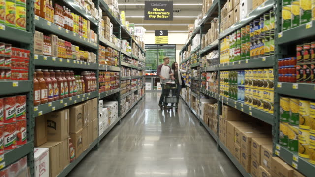 stockvideo's en b-roll-footage met young couple shopping in a warehouse supermarket - shelf