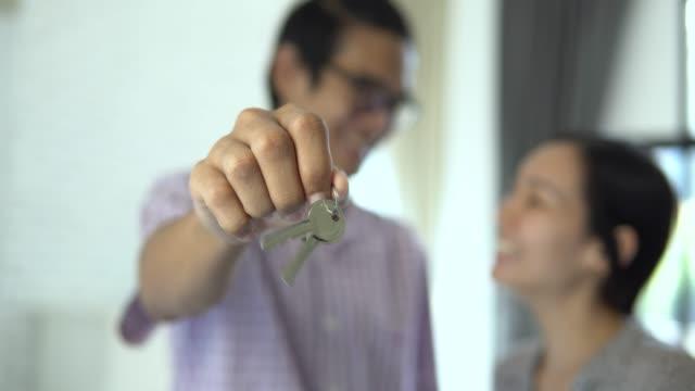 young couple showing keys and kissing each other - house key stock videos & royalty-free footage