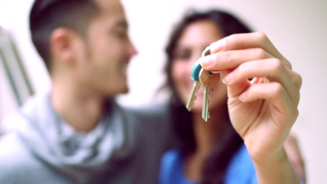 young couple showing keys and kissing each other - moving house stock videos & royalty-free footage