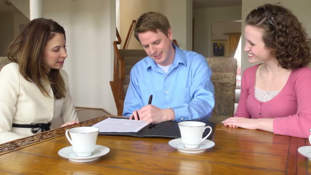 Young Couple Sign Document with Female Professional