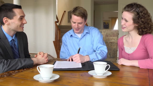 young couple sign document with male professional - contract stock videos & royalty-free footage