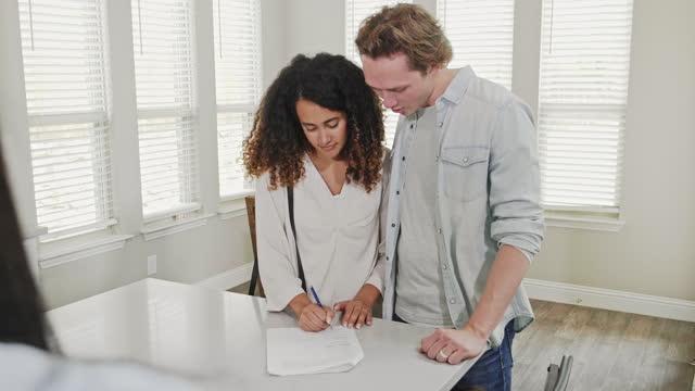若いカップルは、彼らの最初の家の購入のための不動産文書に署名します - 証書点の映像素材/bロール