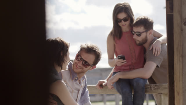 young couple sit and kiss on wooden fence in texas ghost town while friends look at smartphone - rustic stock videos & royalty-free footage