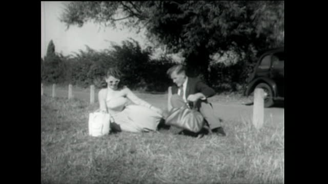 young couple sit down for a picnic in countryside; 1955 - 1955 stock videos & royalty-free footage