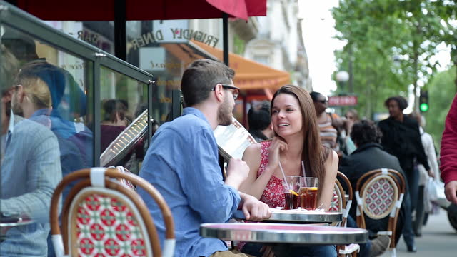 Young couple sit outside and chat over drinks at quaint Parisian diner on the Boulevard Saint-Germain.