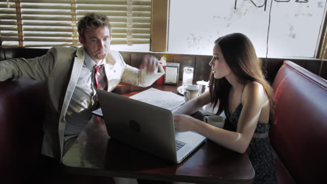 ms young couple sitting and looking together into map and  laptop in american diner / palmdale, ca, united states     - palmdale stock videos and b-roll footage