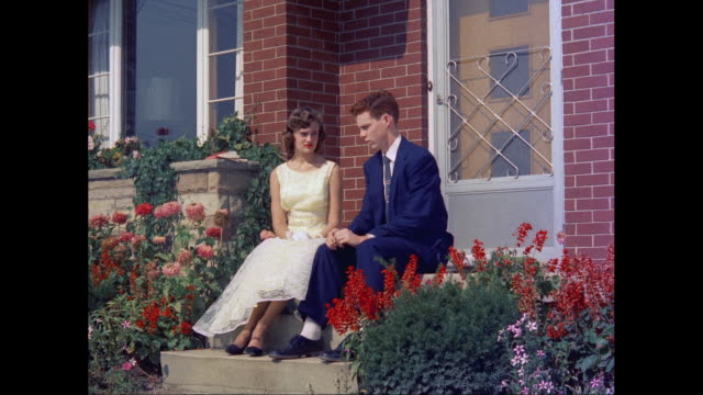 MS Young couple sitting and talking in front of house / United States