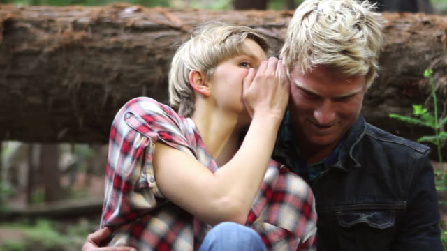 ms young couple sitting and whispering in front of a fallen log over creek in redwood forest / big sur, california, usa - whispering stock videos & royalty-free footage