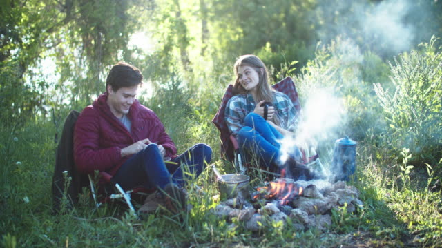 young couple sitting around a campfire - girlfriend stock videos & royalty-free footage