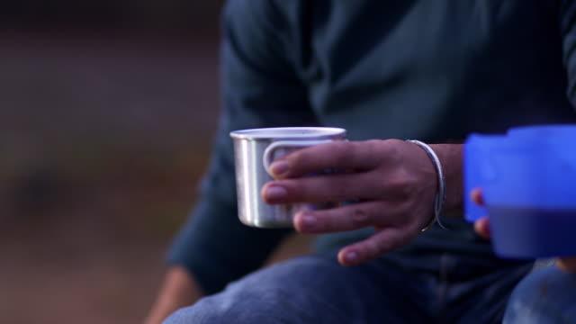 vídeos y material grabado en eventos de stock de cu young couple sitting around campfire  drinking pouring from kettle  - tetera vajilla