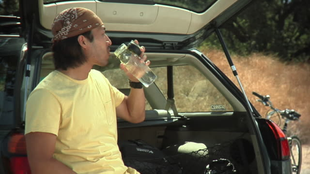 ms young couple sitting at back of car drinking water / malibu creek, california, usa - land vehicle stock videos & royalty-free footage